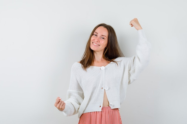 Young lady in cardigan and skirt showing winner gesture looking blissful isolated