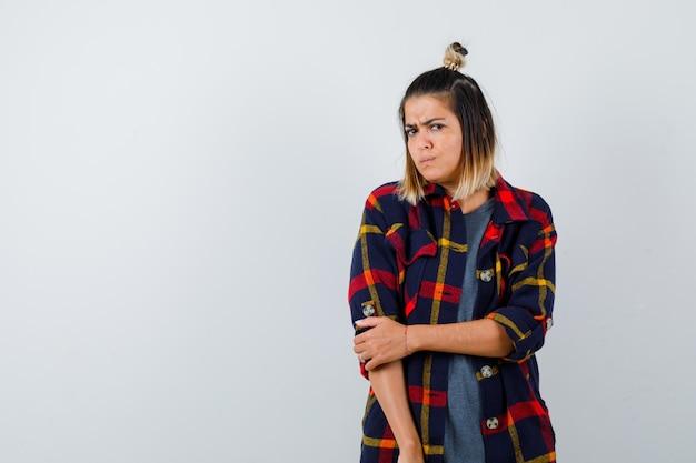 Giovane donna in camicia casual a quadri guardando la fotocamera e guardando triste, vista frontale.