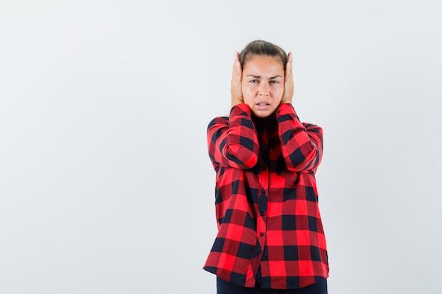 Giovane donna in camicia casual stringendo la testa tra le mani e guardando infastidito, vista frontale.