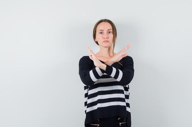 Giovane donna in camicia casual che fa gesto di arresto e che sembra risoluta