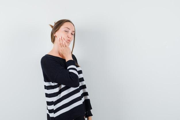 Giovane donna in camicia casual che tiene la mano sulla guancia e che sembra esitante