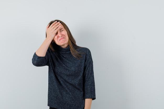 Giovane donna in camicia casual tenendo la mano sulla fronte e guardando triste