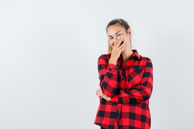 Giovane donna in camicia casual tenendo la mano sulla bocca e guardando felice, vista frontale.