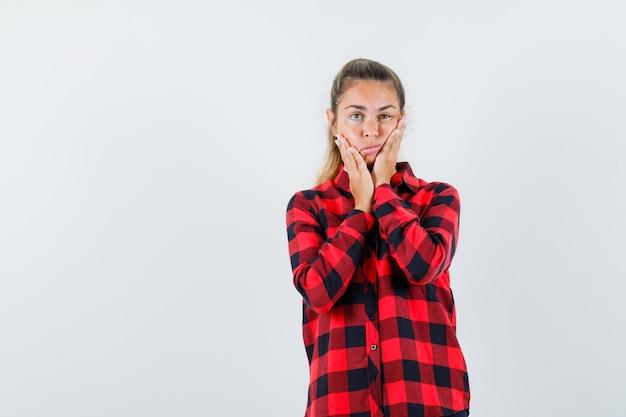 Giovane donna in camicia casual che tiene le mani sulle guance e sembra impotente, vista frontale.