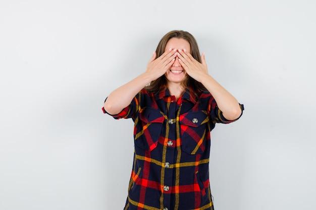 Giovane donna in camicia casual tenendo le mani sugli occhi e guardando allegro, vista frontale.