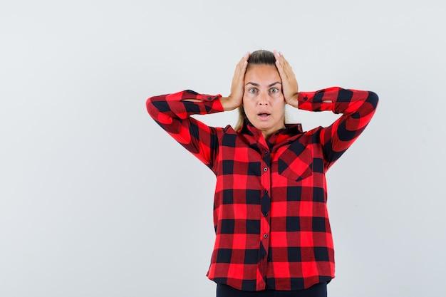 Giovane donna in camicia casual tenendo le mani sulla testa e guardando agitato, vista frontale.