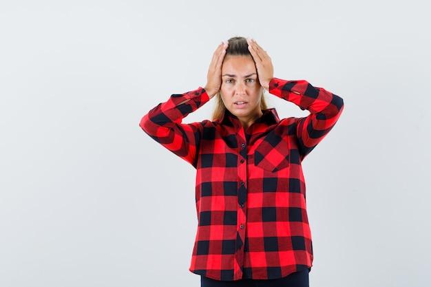 Giovane donna in camicia casual tenendo le mani sulla testa e guardando impotente, vista frontale.