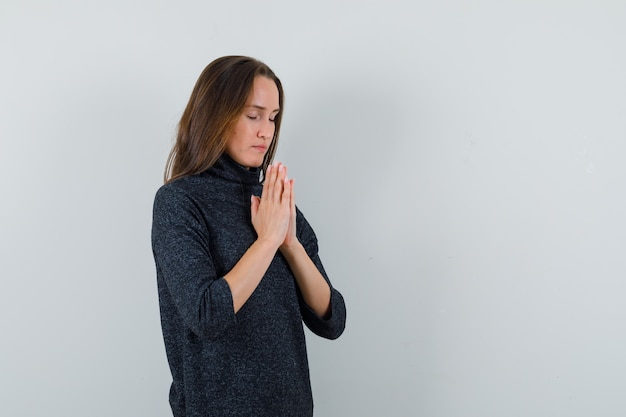 Giovane donna in camicia casual mano nella mano nel gesto di preghiera e che sembra calma