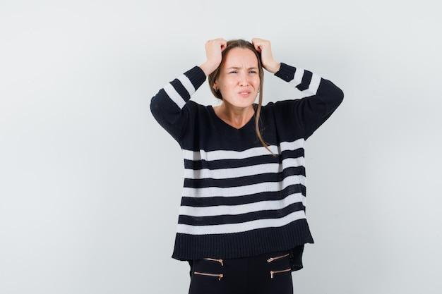 Giovane donna in camicia casual mantenendo le mani sulla testa e guardando dispiaciuto