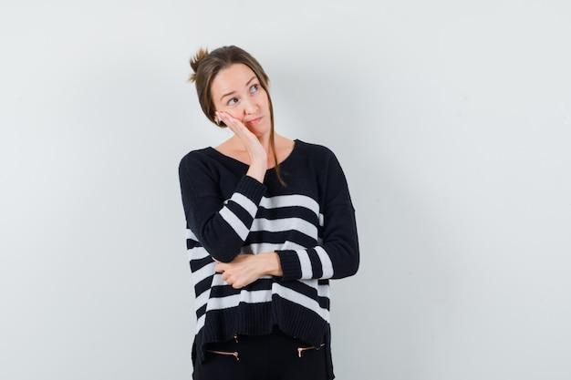 Giovane donna in camicia casual appoggiata sulla guancia sul palmo e guardando pensieroso