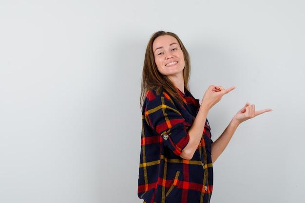 Giovane donna in camicia casual che punta a destra e sembra felice, vista frontale.