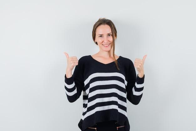 Giovane signora in camicia casual che mostra i doppi pollici in su e che sembra felice