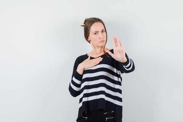 Giovane donna in camicia casual che mostra il gesto di arresto e che sembra seria