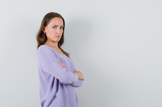 Giovane donna in camicia casual in piedi con le braccia incrociate e che sembra triste