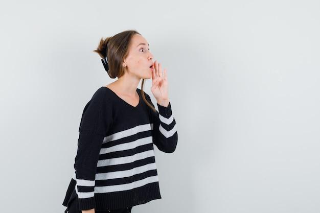 Giovane donna in camicia casual che dice il segreto con la mano vicino alla bocca