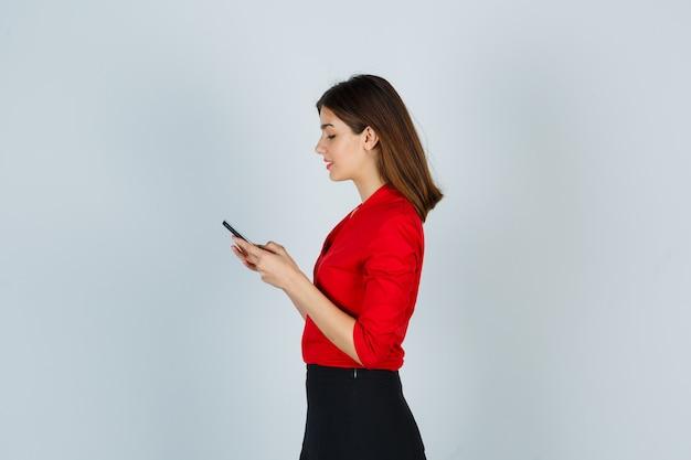 Giovane signora che chiacchiera sul telefono cellulare in camicetta rossa, gonna e sembra felice