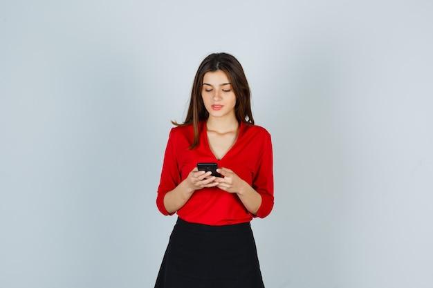 Молодая леди разговаривает по мобильному телефону в красной блузке, юбке и выглядит счастливой