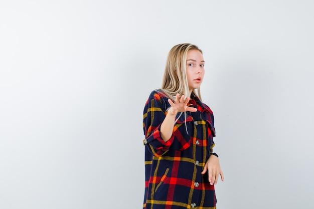 Giovane donna in camicia a quadri che fa cenno a qualcuno in avanti e sembra fiduciosa, vista frontale.