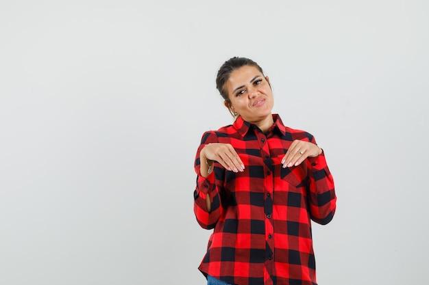 Giovane donna in camicia a quadri facendo un gesto divertente con le mani e guardando divertito