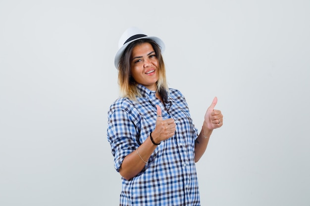 Young lady in checked shirt hat showing double thumbs up and looking confident