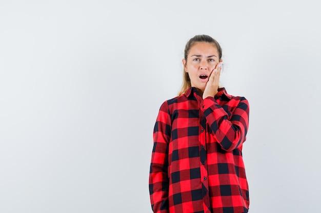 Giovane donna in camicia a quadri tenendo la mano sulla guancia e guardando smemorato