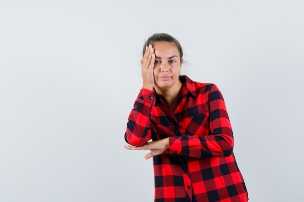 Giovane donna in camicia a quadri tenendo la mano sulla guancia e guardando pensieroso