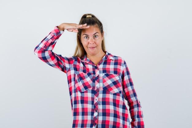 Giovane donna in camicia a quadri che guarda l'obbiettivo con la mano sopra la testa e guardando stupito, vista frontale.