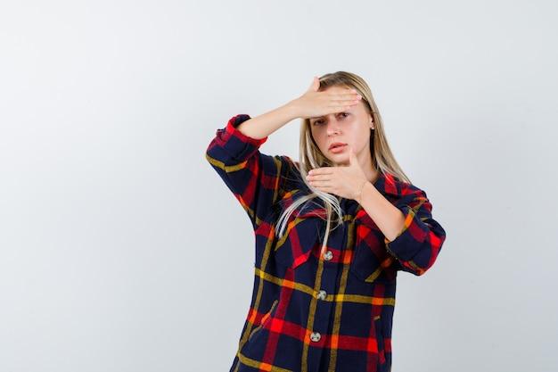 Giovane donna in camicia a quadri che fa il gesto del telaio e guardando fiducioso, vista frontale.