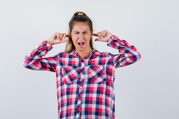 Giovane donna in camicia a quadri tappando le orecchie con le dita e guardando irritato, vista frontale.