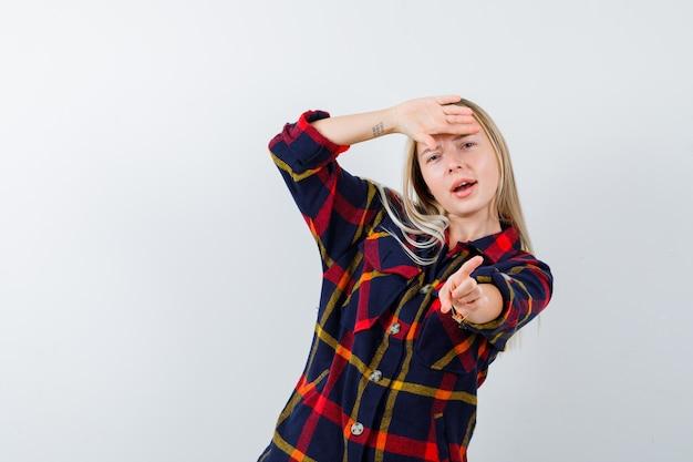 Giovane donna in camicia a quadri che punta da parte tenendo la mano sulla fronte e guardando positivo, vista frontale.