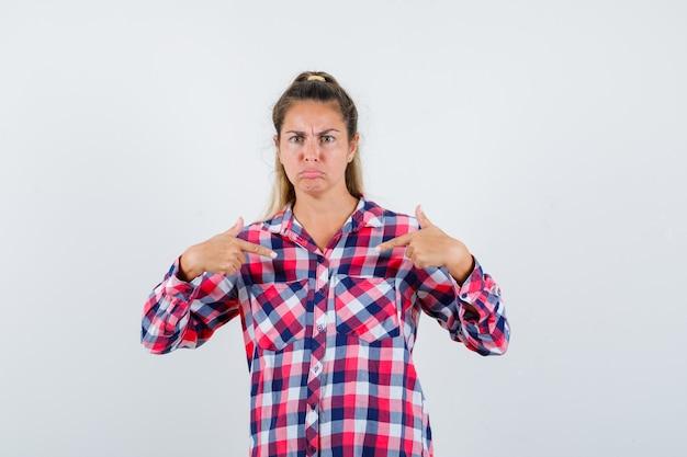 Giovane donna in camicia a quadri che punta a se stessa e che sembra seria, vista frontale.