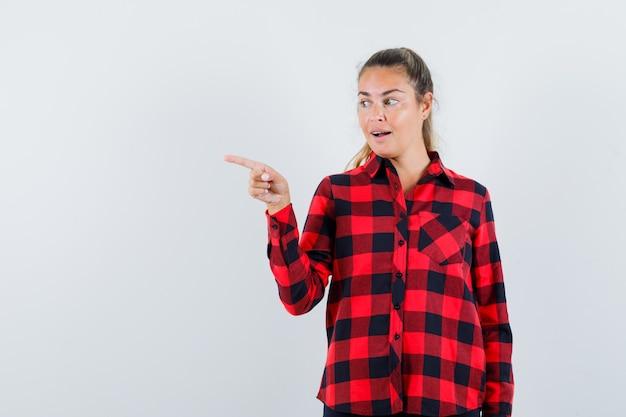 Giovane donna in camicia a quadri che punta verso il lato sinistro e sembra stupita
