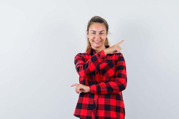 Giovane donna in camicia a quadri che punta all'angolo in alto a destra e che sembra allegra