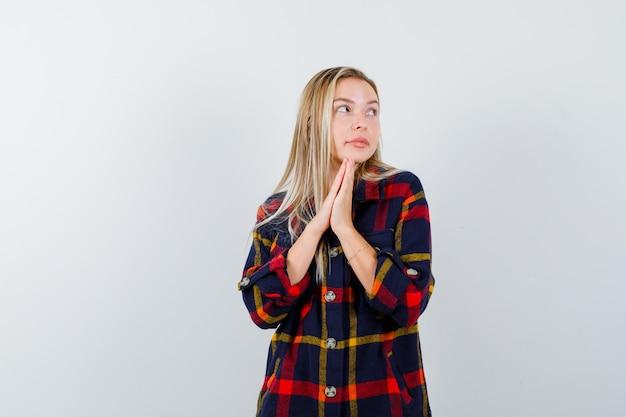 Giovane donna in camicia a quadri premendo insieme le dita per pregare e guardando pacifica, vista frontale.