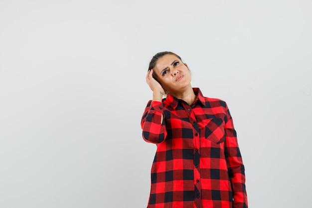 Giovane donna in camicia a quadri graffiare la testa, alzando lo sguardo e guardando pensieroso