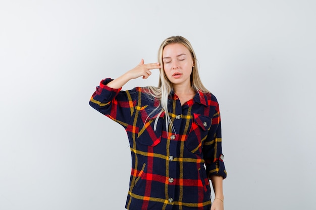 Young lady in checked shirt shooting herself with hand gun and looking hopeless , front view.