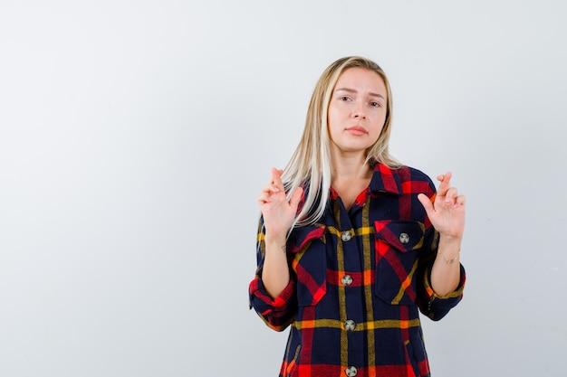 Giovane donna in camicia a quadri che mostra le dita incrociate e sembra speranzoso, vista frontale.