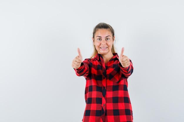Giovane signora in camicia controllata che mostra i doppi pollici in su e che sembra allegra