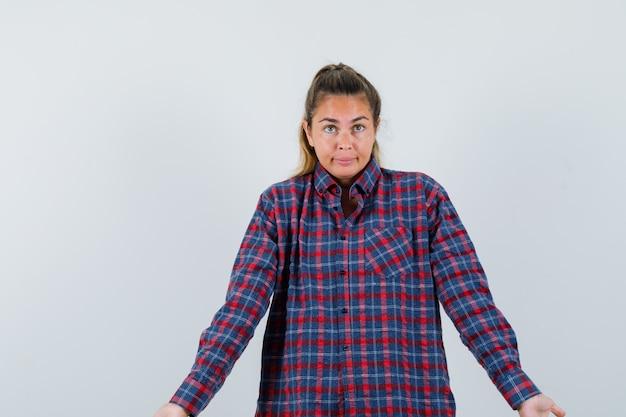 Giovane donna in camicia a quadri che mostra gesto impotente e che sembra confuso, vista frontale.