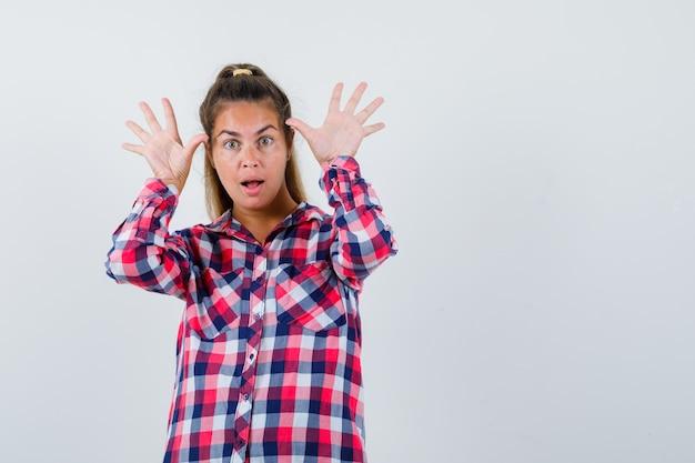 Giovane donna in camicia a quadri che mostra i palmi delle mani, apertura della bocca e sguardo stupito, vista frontale.