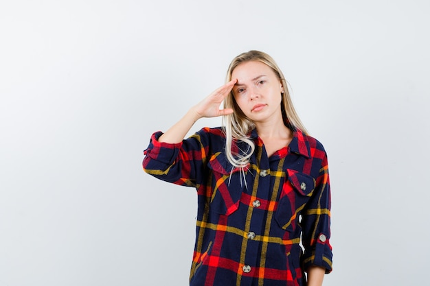 Young lady in checked shirt showing salute gesture and looking confident , front view.