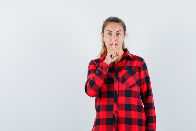 Young lady in checked shirt showing silence gesture and looking careful