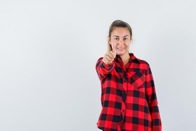 Giovane signora in camicia controllata che mostra il pollice in su e sembra allegra