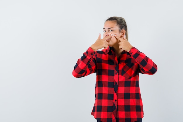 Young lady in checked shirt squeezing her pimple on her cheek