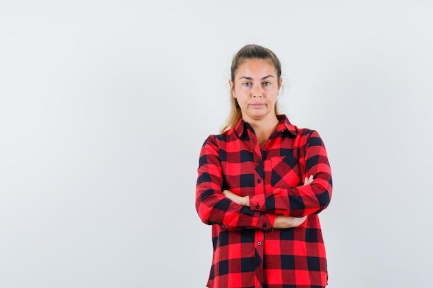 Giovane donna in camicia a quadri in piedi con le braccia incrociate e guardando fiducioso