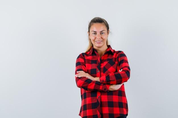 Giovane donna in camicia a quadri in piedi con le braccia incrociate e guardando allegra