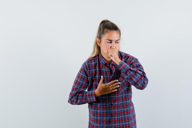 Giovane donna in camicia controllata che soffre di tosse e sembra malata, vista frontale
