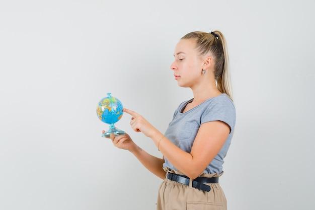 Giovane donna che sceglie la destinazione sul globo terrestre in maglietta, pantaloni e guardando pensieroso.