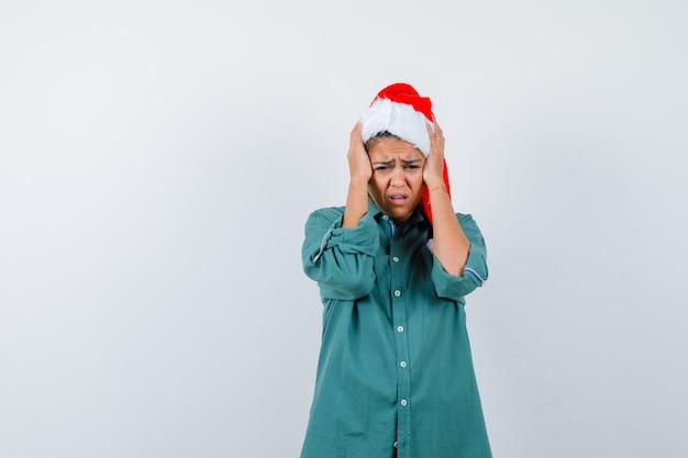 Giovane donna con cappello natalizio, camicia che stringe la testa con le mani e sembra addolorata, vista frontale.
