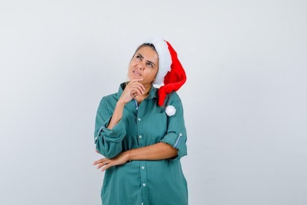 Giovane donna con cappello di natale, camicia e sguardo premuroso, vista frontale.
